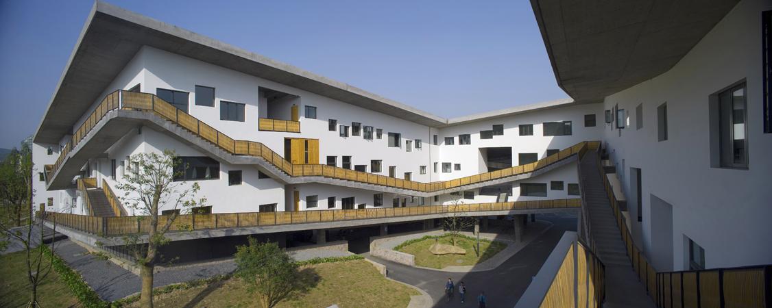 Escaleras de concreto recorren la fachada de un edificio de la Academia de Artes de China, campus de Xiangshan fase II.