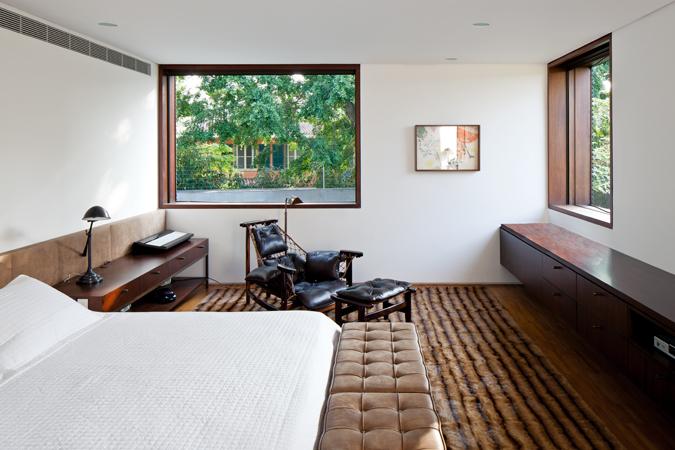El dormitorio principal ocupa la caja de madera que sobresale en el primer nivel. Destacan los muebles en madera oscura como la Cadeira Jangada de Jean Gillon.
