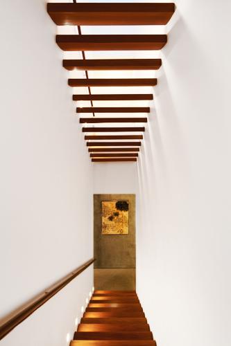 La escalera ocupa el espacio central de la casa. Los escalones de madera sin contra huella permiten el ingreso de la luz cenital.