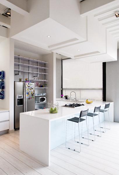 La cocina adopta este gran mesón de quarztone como comedor, mesa bar y zona para cocinar. Los cubos adosados a la cubierta demarcan el espacio.