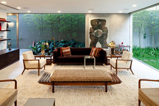 Ventanas corredizas abren la sala de estar hacia el fondo y el patio lateral. Los colores claros de los muebles y el tapete contrastan con el sofá en el centro de la foto.