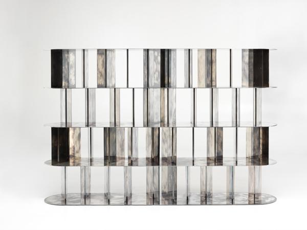 La biblioteca DC 218, diseñada por Vincenzo De Cotiis para la firma Ceccotti Collezioni, tiene una estantería modular con elementos apilables disponibles en latón con acabado en plata o en nogal.