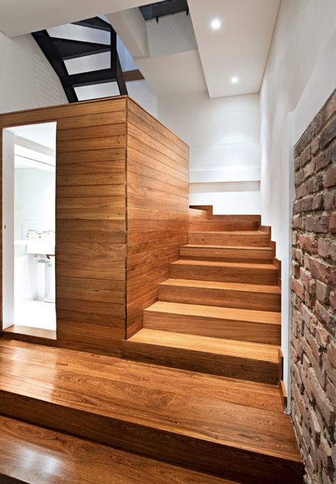 La escalera de madera envuelve y cubre el baño.
