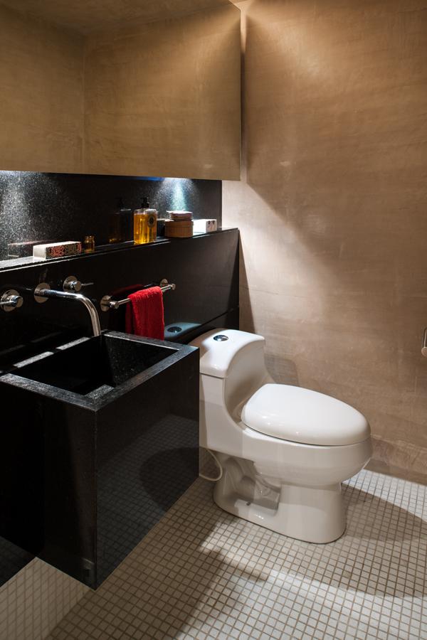 El lavamanos está compuesto por una pieza de mármol San Gabriel. Para darle amplitud al espacio se instalaron luces indirectas y un espejo dilatado.