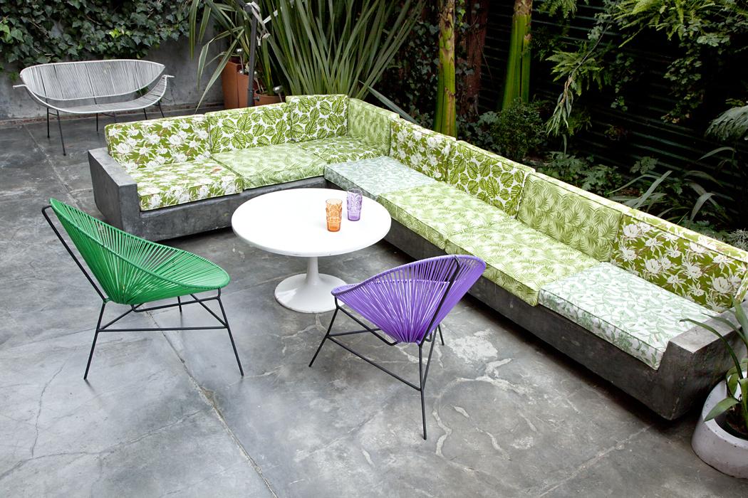Los cojines del sofá están cubiertos con lonas impermeables Lafayette, que conservan el estilo selvático.