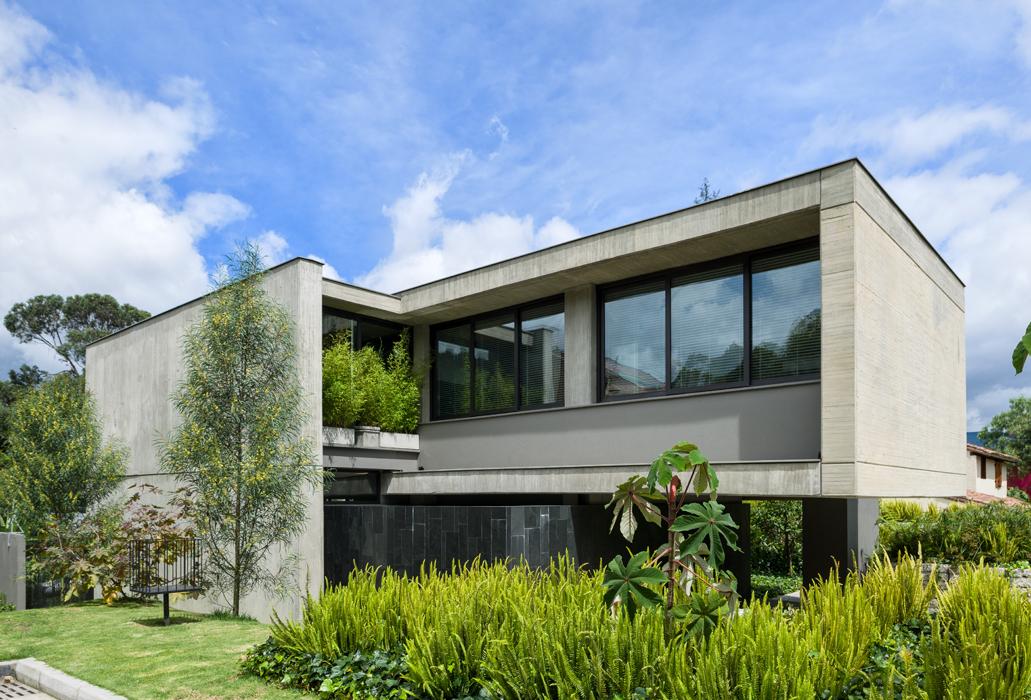 Grandes ventanales de piso a techo comunican la sala y el comedor con los jardines.