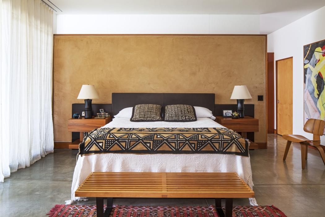 El cuarto principal tiene una onda étnica. La cama fue hecha por el arquitecto, quien también es diseñador, y las mesas de noche están incorporadas al espaldar, que es de cuero. La manta es africana; los cojines y el cobertor son de Monterí.