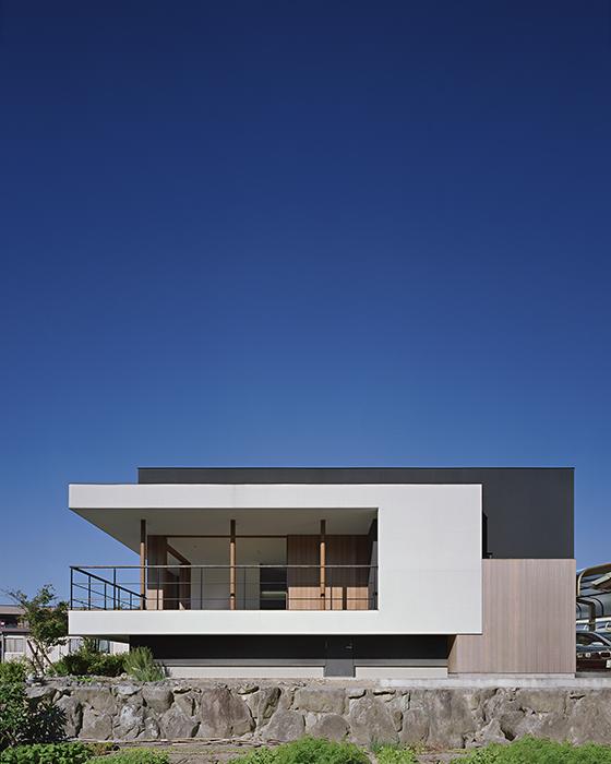 Al proyectarse sobre los cimientos, el pequeño volumen blanco disminuye la apariencia del negro, el más grande, y minimiza su impacto entre las casas vecinas.