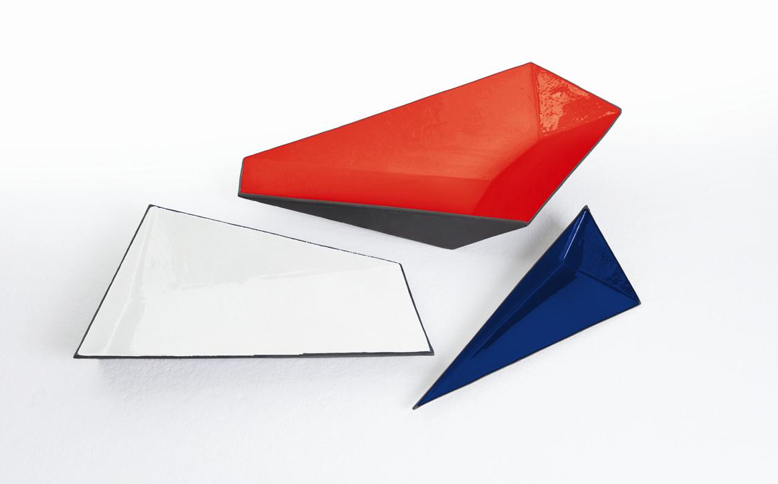 Formas angulares generan tensión visual en estos fruteros o bowls. Su interior de color contrasta con lo opaco de su exterior.
