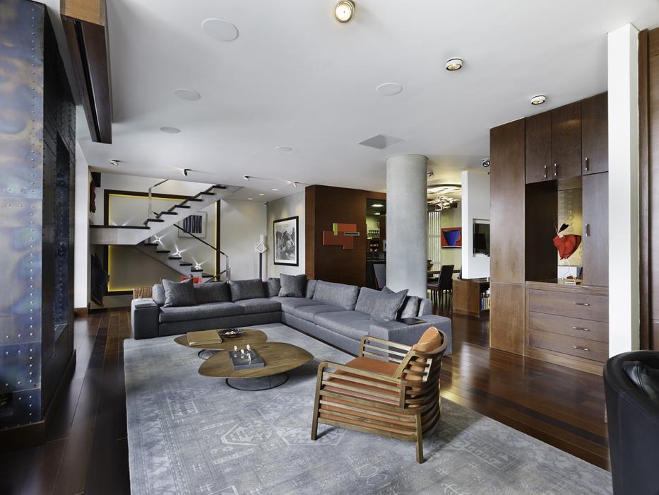 La escalera de concreto, con una baranda de acero y madera, articula los tres pisos de la casa y está enmarcada en un cuadrado de madera.