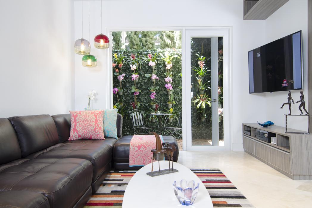 El sofá, de cuero gastado, es de Restoration Hardware. Los cojines son de Pepa Pombo Home, el tapete es de FAB y la mesa de centro es una Eames Elliptical Table, diseño de Charles y Ray Eames para Herman Miller.