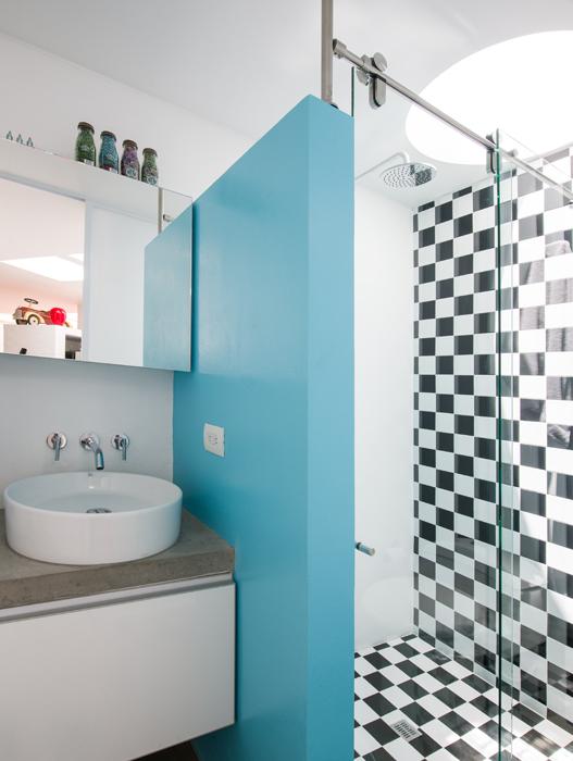 El baño social es quizá la zona más irreverente de la casa, especialmente por las dos vitrinas redondas que yacen en el piso –dentro de las cuales el propietario puso objetos no convencionales– y el enchape de ajedrez.
