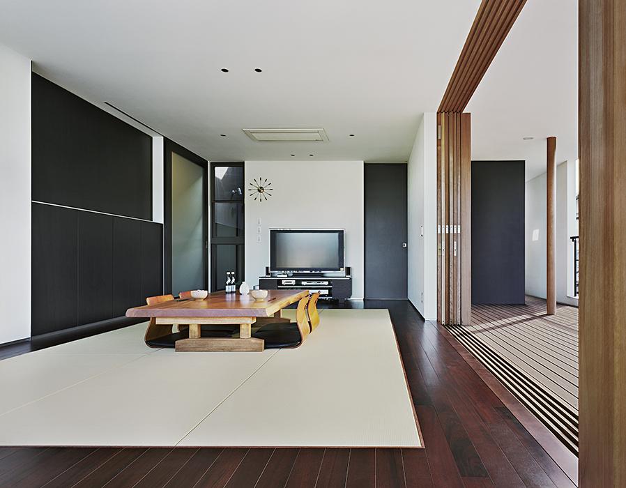 En la sala de tatami una mesa chabudai y una pantalla plana de video coexisten en armonía.