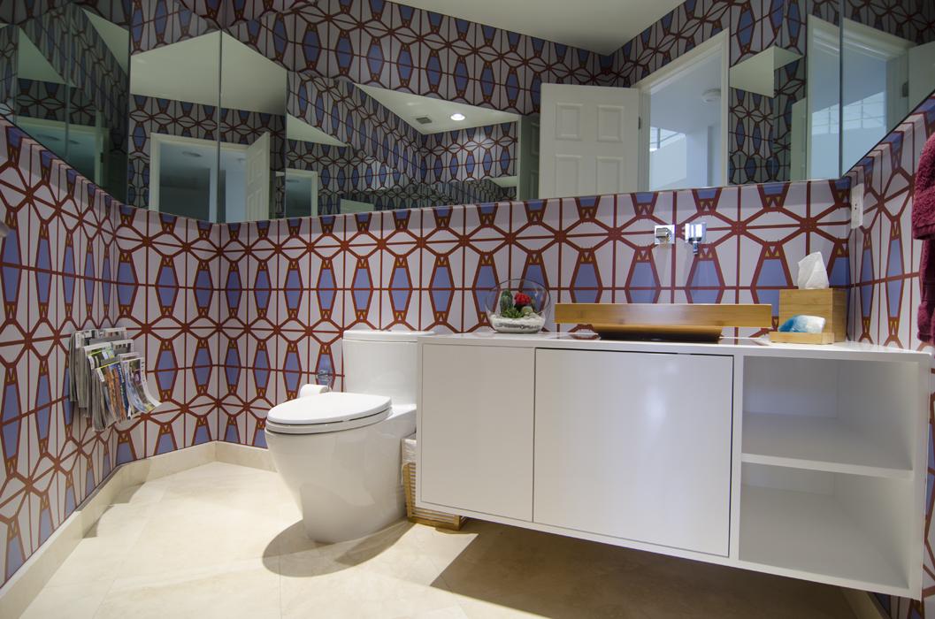 Para el baño social, con una marcada forma triangular, se utilizó un lavamanos de sobreponer de bambú encima del mueble blanco de poliuretano. Además, se creó un interesante juego de espejos que genera diferentes reflejos.