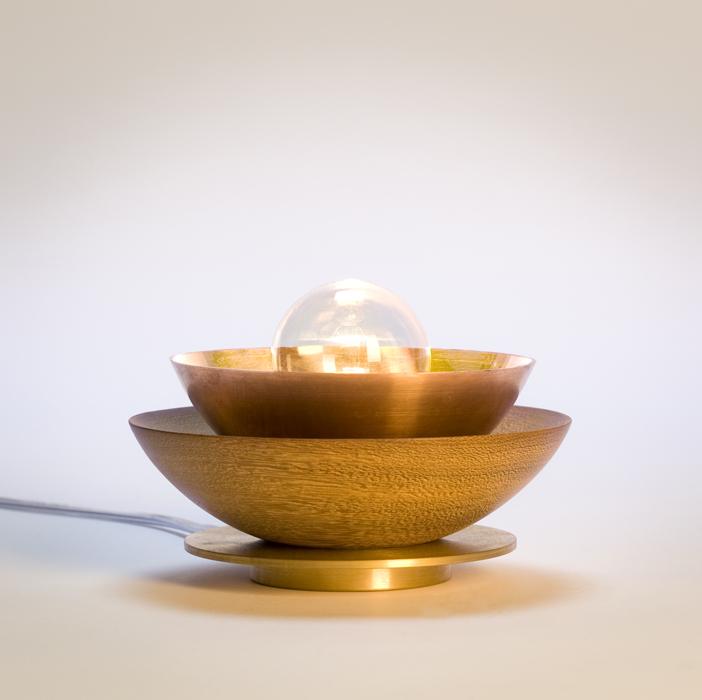 Esta lámpara, bautizada Candil, está fabricada en cobre y latón, que son óptimos conductores, con una base de madera que actúa como aislante.