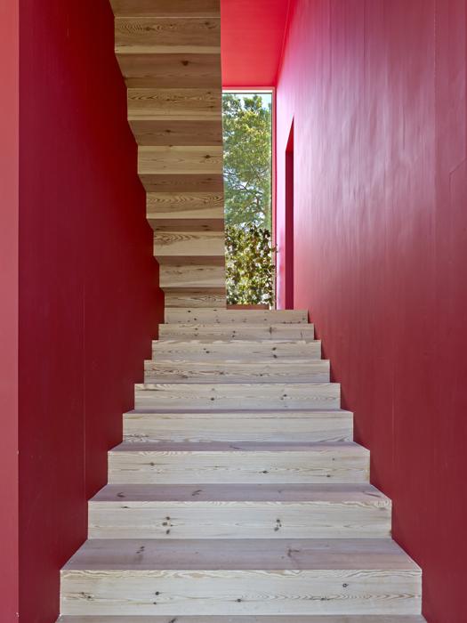 El rojo de la caja de la escalera rompe la neutralidad de la paleta de tonos y refleja el color del cobertizo donde Isaac y Andrew guardan su velero.