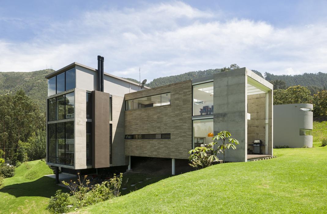 Planos de vidrio, concreto y ladrillo, sumados a las aplicaciones de pintura gris, integran la arquitectura de la casa con el entorno natural.