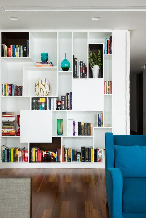 La biblioteca, hecha de madera con laca catalizada blanca, presenta un diseño con líneas de 90 grados que equilibra las formas curvas de los floreros.