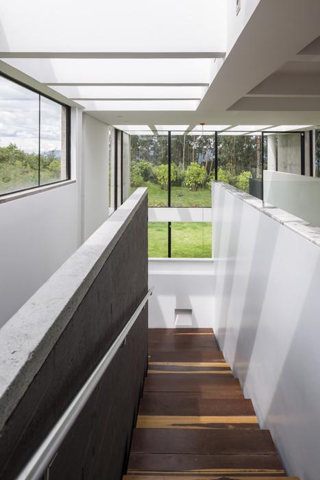 Una alargada escalera de dos tramos sirve de caja de luz y da amplitud y claridad al diseño interior de la casa.