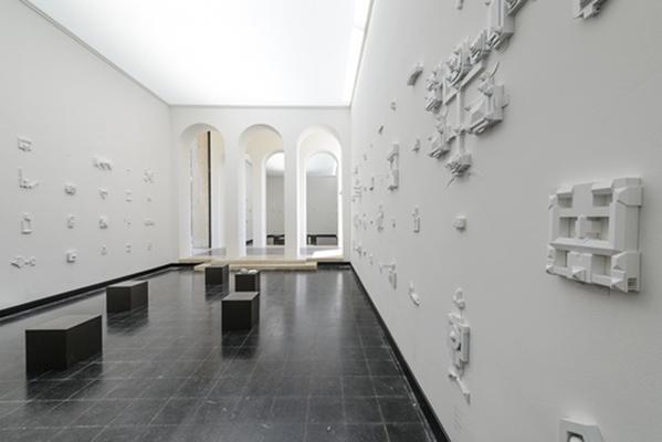 Detalle de una de las más de doscientas maquetas de edificios de Parlamentos Nacionales de todo el mundo que emergen del muro de la sala principal del pabellón.