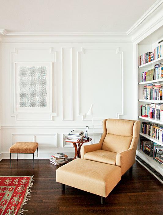 En uno de los rincones de la sala se encuentra la biblioteca con un sillón para la hora de la lectura que los dueños compraron de segunda mano. El cuadro, dibujo sobre papel, es de Hadieh Shafie.