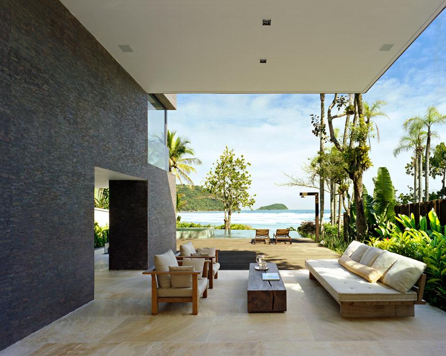 Entre la sala y el deck sobre la piscina, un estar sombreado marca la transición interior-exterior. La madera rústica y los tapizados crudos de los muebles integran la decoración con el entorno natural.