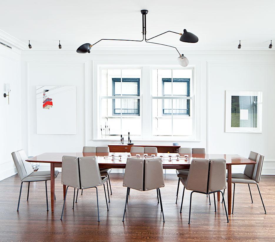 El blanco como telón de fondo es protagonista en el comedor. Una chandelier, de Serge Mouille, se encarga de darle luz al espacio. La mesa de madera es de Florence Knoll y está rodeada por ocho sillas de Pierre Guariche.