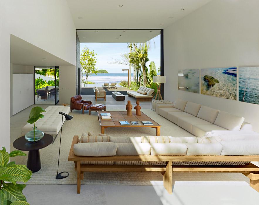 Adornada principalmente por la vista de la costa y el océano, la sala tiene muebles de diseñadores brasileños, entre ellos Arthur Casas, autor del sofá de madera clara. La silla Mole, tapizada en cuero colorado, es de Sergio Rodrigues.