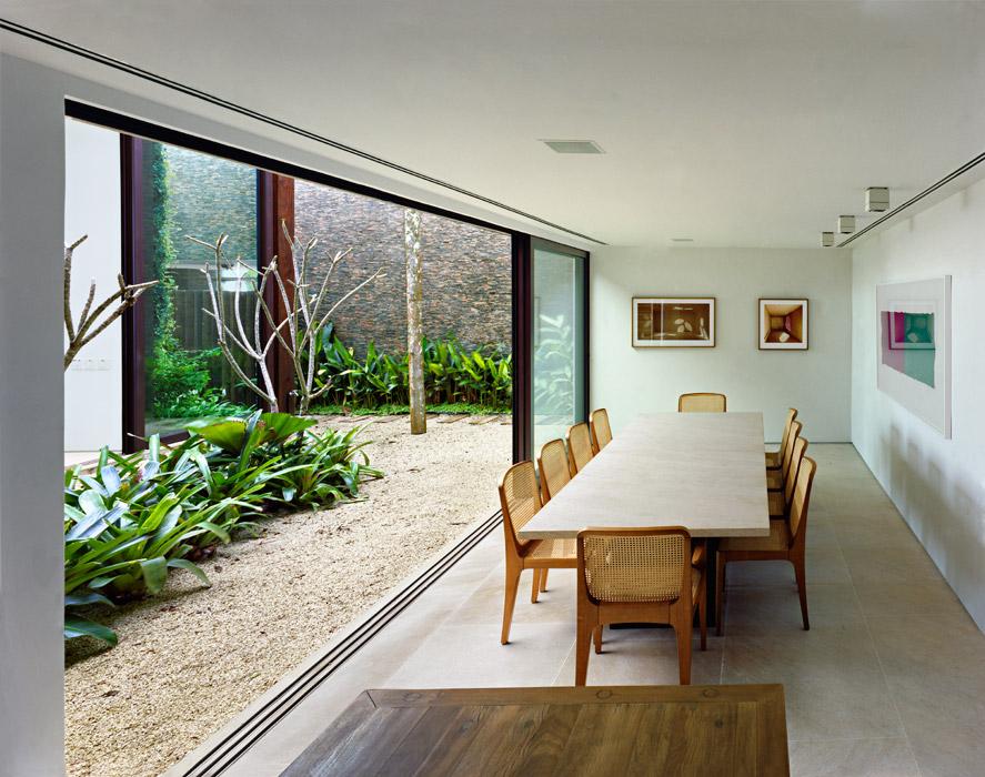En el comedor, una mesa con tapa de mármol sobre una base de metal, del estudio de Arthur Casas.