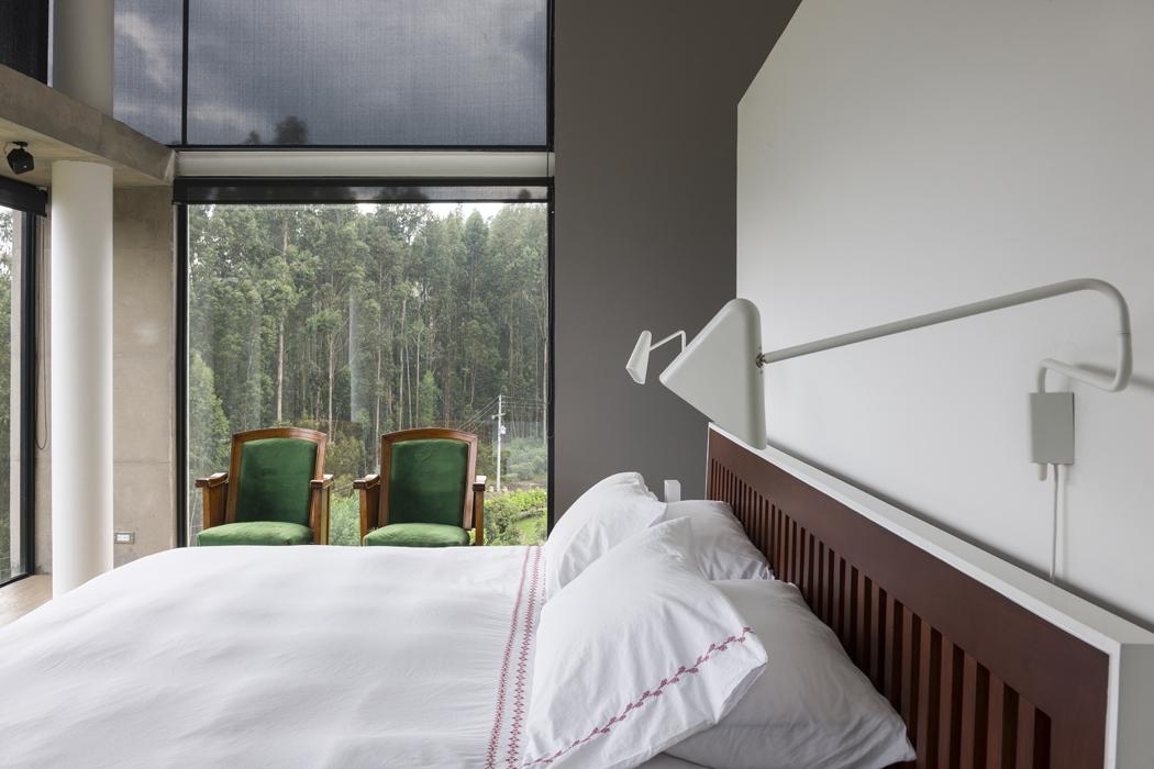 Rodeada por ventanales de doble altura, la alcoba principal es un mirador sobre el bosque y la sabana.