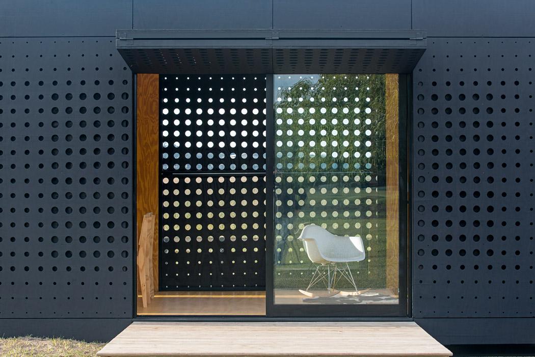 El panel de madera perforada se pliega y abre por completo para generar una protección horizontal al costado de la vivienda. La mecedora Eames Plastic Armchair transmite una sensación de descanso y ocio.