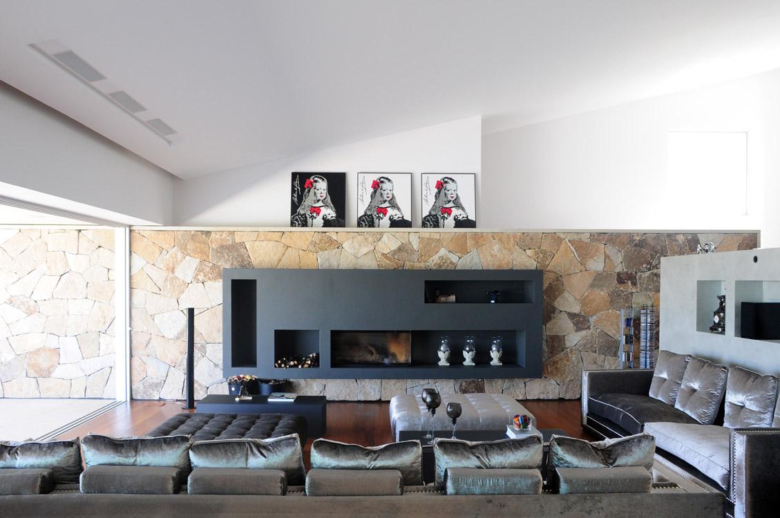 Entre el piso de madera y el techo inclinado blanco de la sala, el muro de fondo marca una franja de piedra, que contiene la chimenea en gris pizarra, y se prolonga al exterior para formar el remate de la piscina.