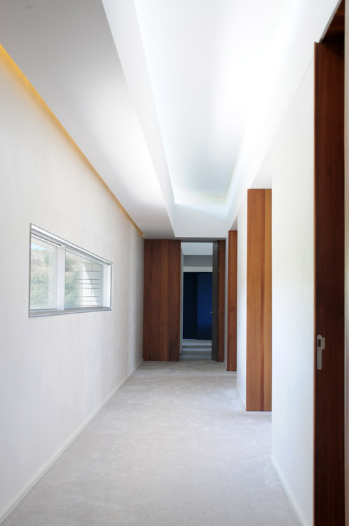 El desfase de las cubiertas permite la iluminación cenital indirecta de la circulación del segundo piso. Las ventanas en la fachada norte se abren a la vista del valle del Tajo.