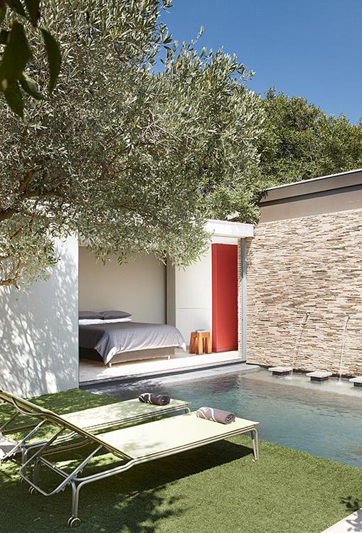 La articulación entre el interior y el exterior fue explotada al máximo para borrar los límites. El dormitorio tiene una conexión directa con la piscina. Las reposeras son de diseño italiano. La pared exterior está recubierta de pizarra.