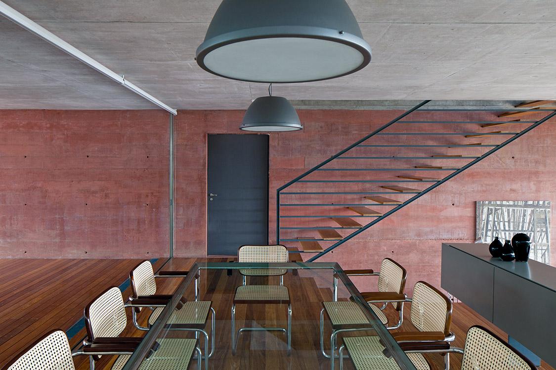 """La forma de la escalera acompaña la dirección del espacio, sin interrumpir la continuidad. Las sillas """"Cesca"""" del comedor son diseño del arquitecto Marcel Breuer."""