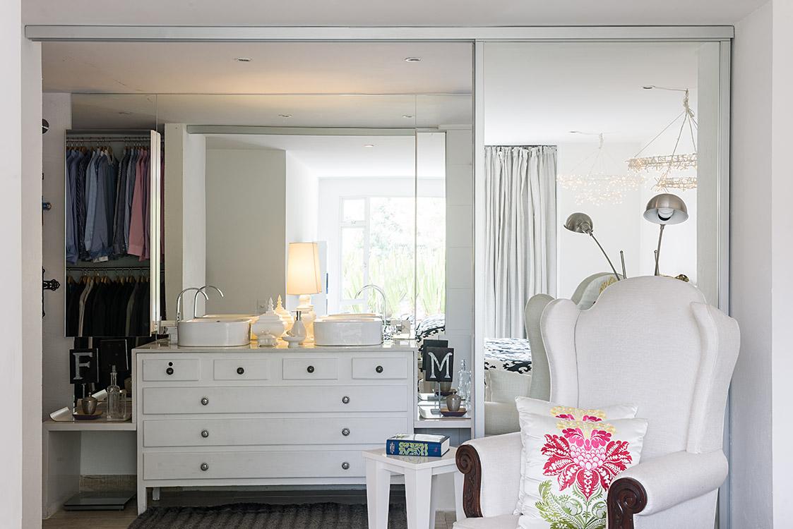 Detrás de las puertas de espejo y encima de un escaparate con placa de mármol se ubicaron dos lavamanos. En este vestier diversos accesorios de Anthropologie sirven para guardar objetos.