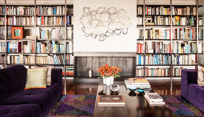 Los parales de acero inoxidable anclados a la pared y sostenidos a presión entre piso y cubierta soportan los estantes volados de color wengué. La obra abstracta de la serie Poliedros es de Rosario López.