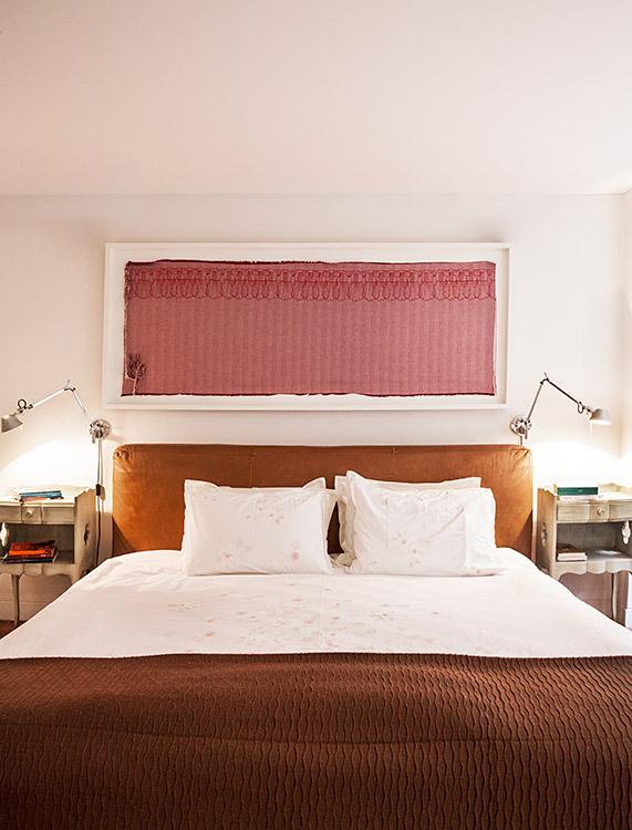 En la habitación principal  se mantiene la combinación  de estilos que está presente  en el resto del apartamento.  Las mesas de noche tienen  un acabado de white wash que contrasta con el cuero coñac de la cama, sobre la cual cuelga una obra de Ana María González.