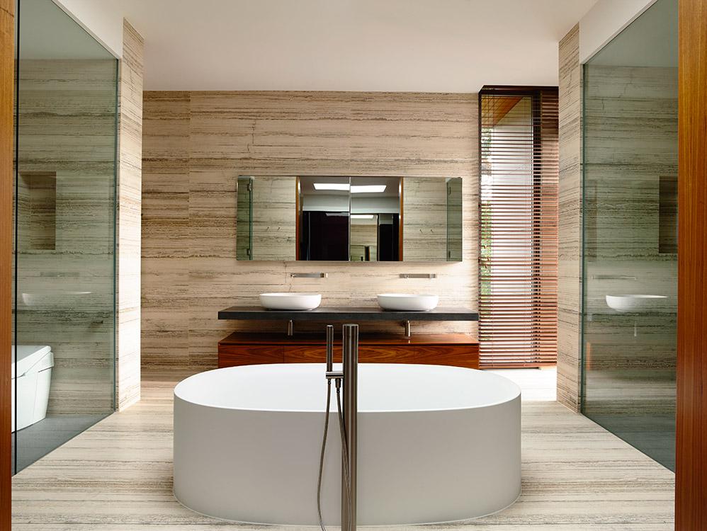 Abajo a la izquierda. El listado del mármol travertino juega con el tramado de la persiana de madera en el baño principal, dispuesto  en torno a la tina.  A la izquierda está  el sanitario; al frente, los lavamanos, y a  la derecha, la ducha.