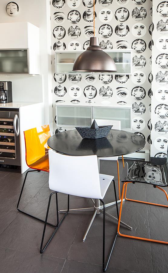 La pared, empapelada con ilustraciones de Piero Fornasetti, y el naranja del acrílico y de las patas de acero inoxidable de las sillas son el atractivo principal de la cocina. La tapa de la mesa es de madera negra, y la base, de acero inoxidable. El comedor completo es de BoConcept.