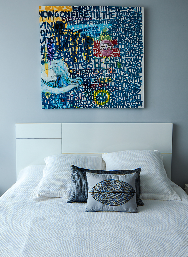 El espaldar de madera lacada, diseñado por Ana María Sardi, tiene líneas de aluminio incrustado que coinciden con el cojín de poliéster brillante gris y el pequeño de rayón. La obra del artista Mauricio Zuluaga proporciona color a la habitación de huéspedes.