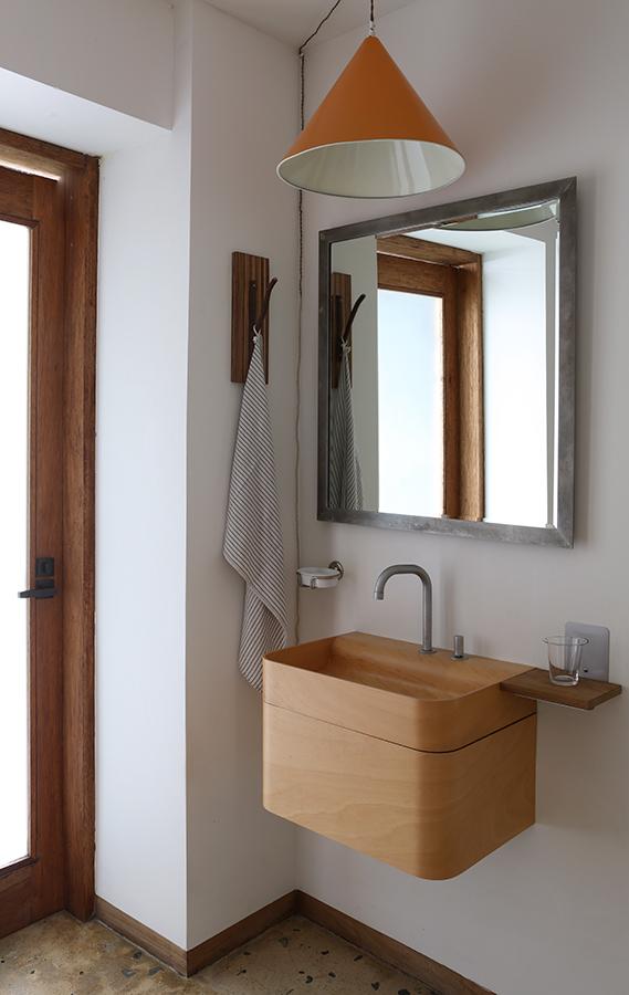 El lavamanos, de madera ash, es italiano. La lámpara naranja es un diseño danés de los años cincuenta. El marco de plata del espejo lo hicieron en Nueva York.
