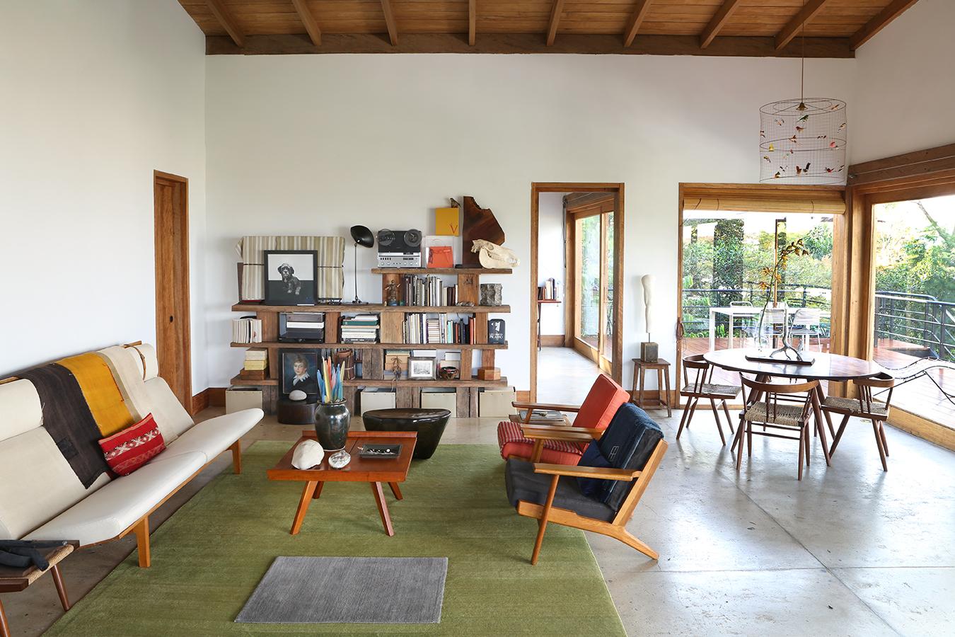 El sofá y las dos sillas de la sala son un diseño sueco de los años cincuenta; el comedor es de George Nakashima. La biblioteca del fondo se construyó con pedazos de madera rústica. Sobre esta hay un óleo de Pucha, la perrita de la dueña, un pastel de 1800 comprado en un anticuario de Nueva York, un Revox suizo de los años sesenta y libros de arquitectura y fotografía.