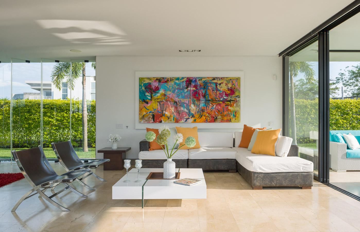 """La sala es un espacio  abierto hacia el exterior amueblado  con un sofá en """"L"""", cojines blancos y sillas de cuero y metal. La mesa blanca de centro es de Carpintería Arquitectónica Alberto del Corte  y el cuadro es de Maki Villamil."""