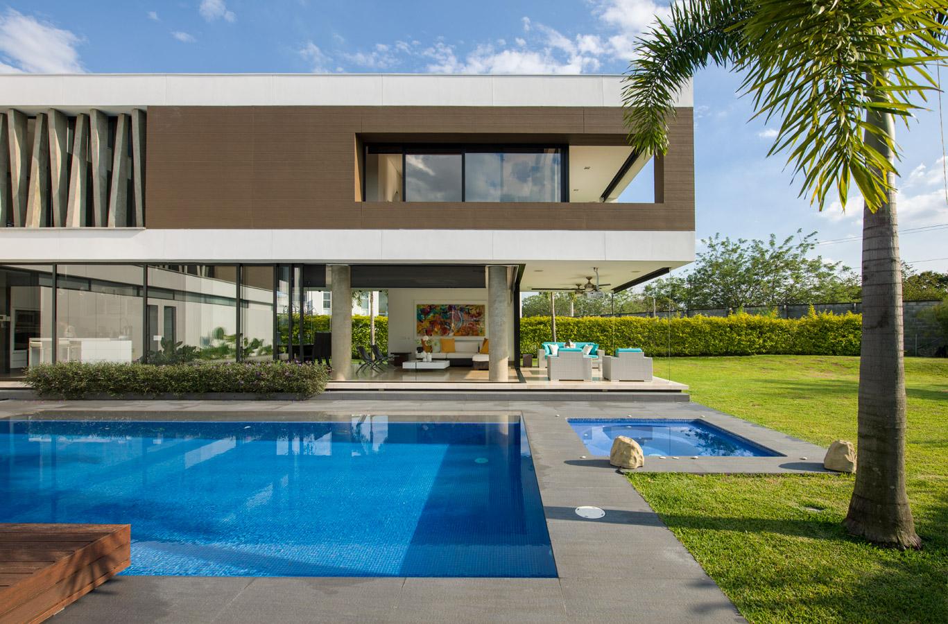 La zona social, transparente y liviana, se expande hacia la terraza donde están la piscina y el jacuzzi, ambos enchapados en baldosines de tono azul fuerte para generar un ambiente alegre.