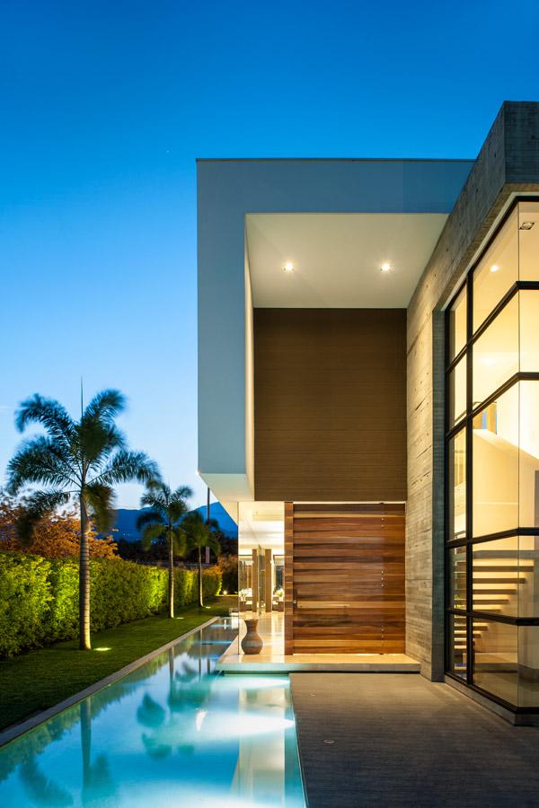 La cerca viva que funciona como cerramiento, las palmeras y el espejo de agua, todo con iluminación indirecta, apoyan los materiales de la edificación: el concreto a la vista, el vidrio, el pañete blanco y el superboard. Resaltan el acceso y la escalera del interior.