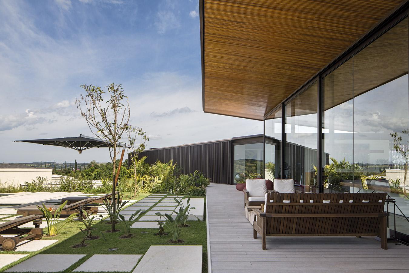 La sala de estar se proyecta hacia el exterior a través de un deck, protegido por el techo que vuela sobre él. Los sillones exteriores son diseño de Carlos Mota.