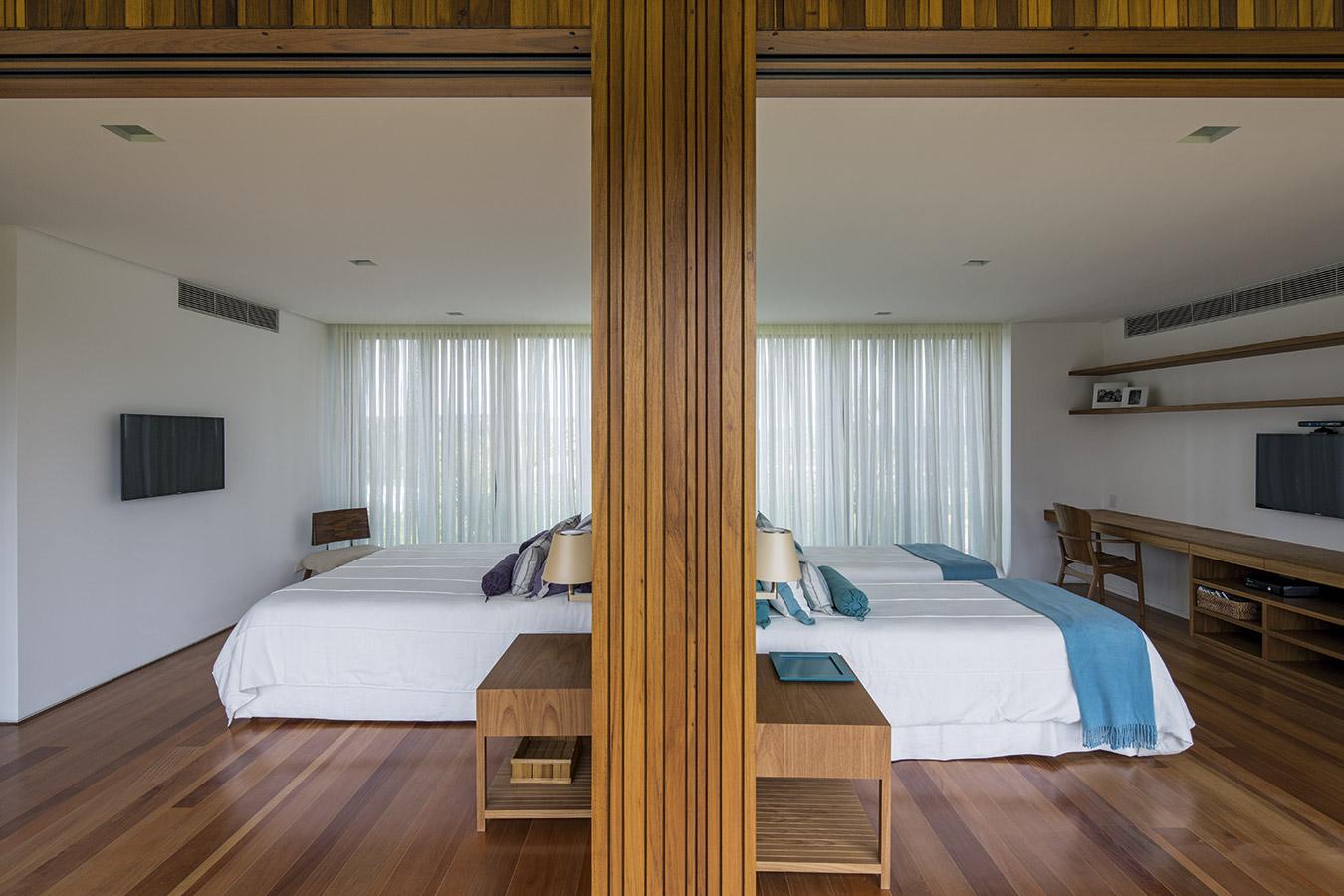 Las puertas correderas dobles, al abrirse por completo, vinculan totalmente los dormitorios con la circulación para permitir la ventilación cruzada y la expansión del espacio.