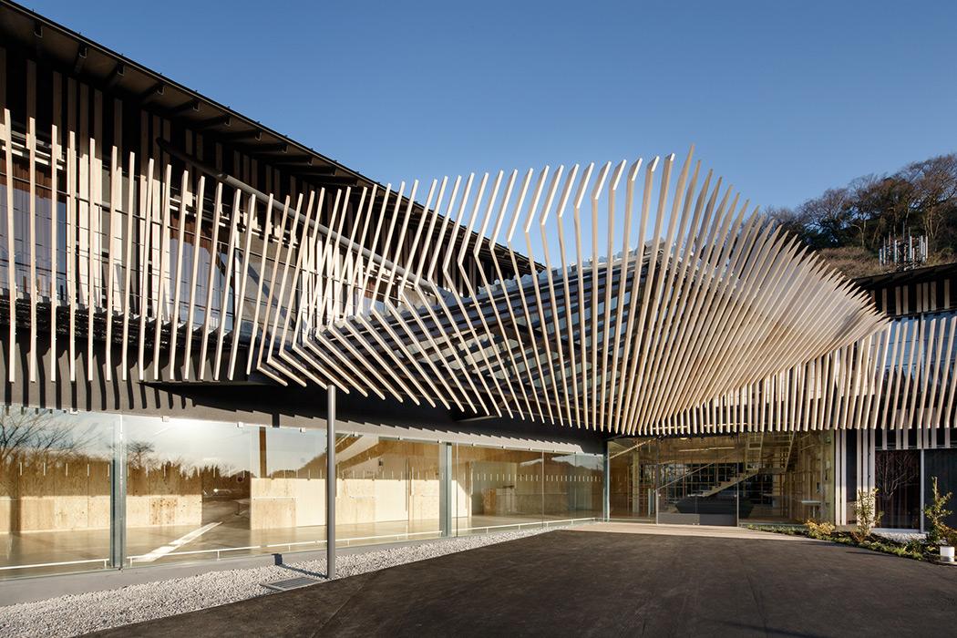 Hayama No Mori es un centro para el cuidado de ancianos durante el día. Su fachada horizontal juega con piezas verticales dobladas de madera que le imprimen dinamismo aerodinámico.