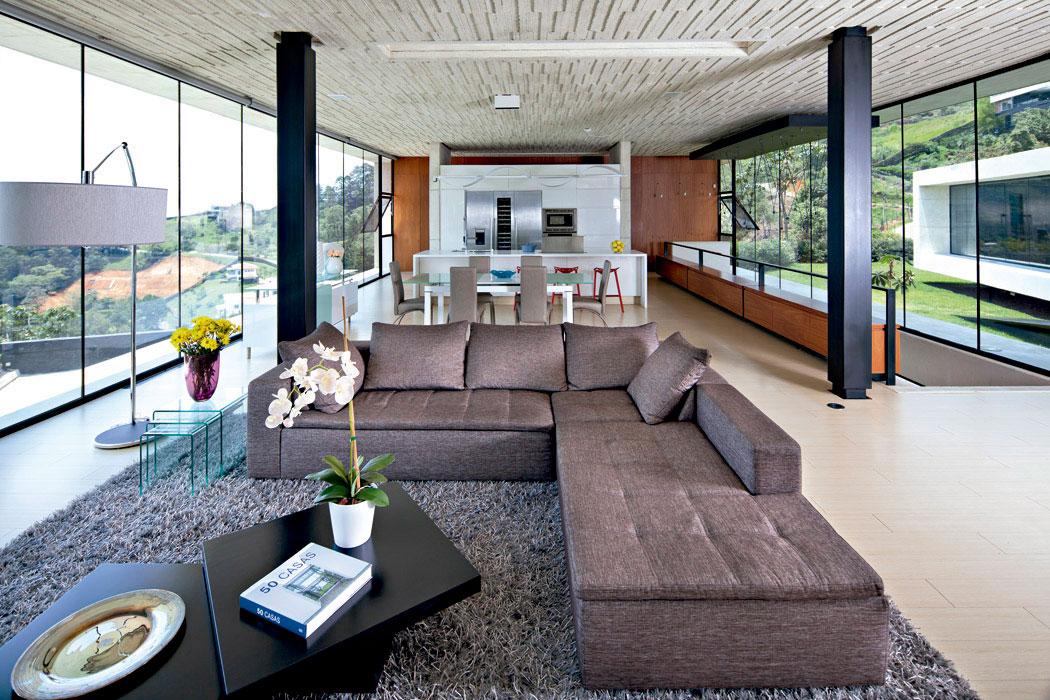 """La sala, con un sofá en """"L"""" tapizado en lino tono tabaco, sobre un tapete de hebras largas color pizarra, comparte el espacio con el comedor y la cocina blanca con accesorios de acero inoxidable. La escalera de caracol, al fondo, conduce al área de servicios."""